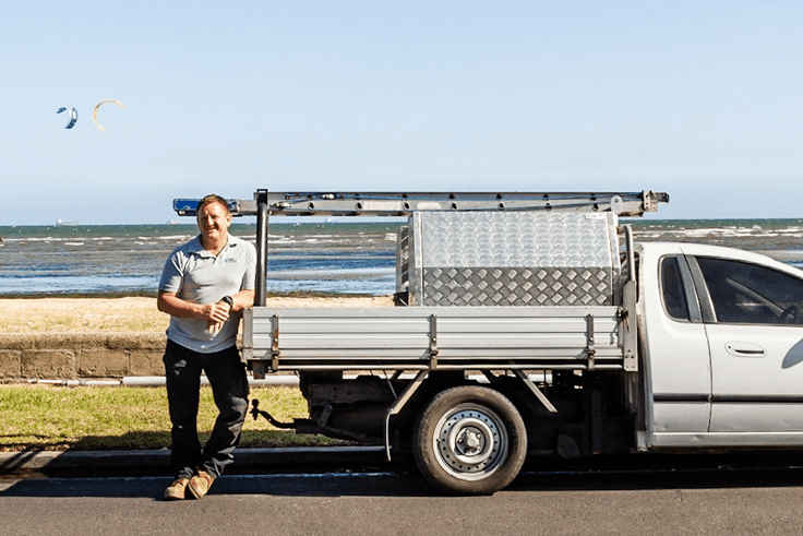 Plumber standing by ute with sea in the background