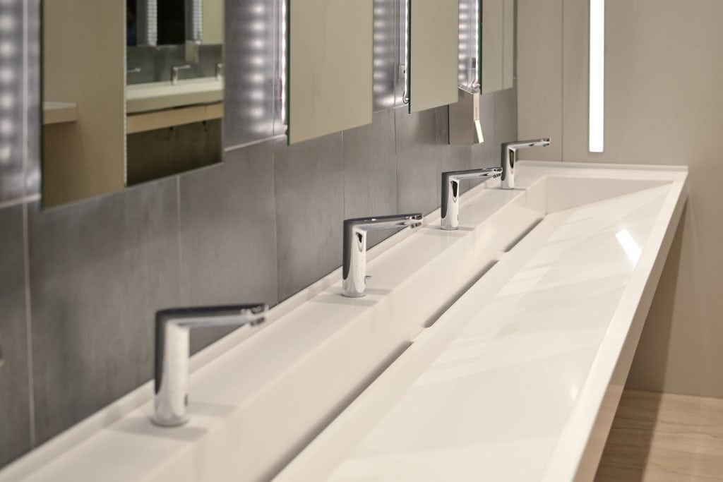 Row of taps and mirrors in a commercial bathroom