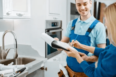 PLumber looking at someone signing paper