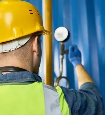 Man in hard hat looking a pressure guage