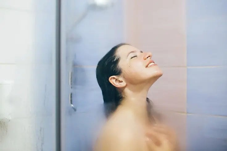 woman behind fogged glass enjoying a hot shower