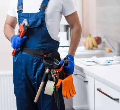 Plumber in kitchen with plumbing tool belt and wrench