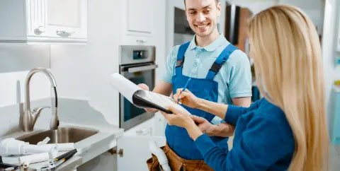 Woman signing a document held out by a plumber