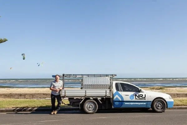 Nick Rice standing beside an NJR Plumbing ute with the sea in the background