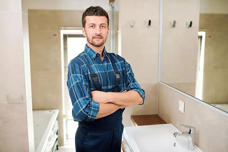 plumber with arms crossed standing in bathroom